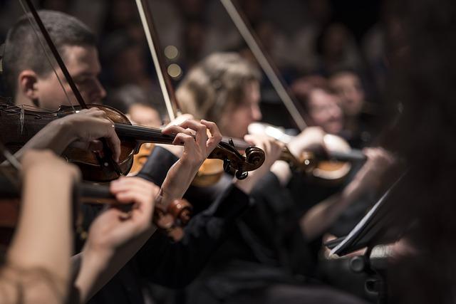 violin players performing on dark stage