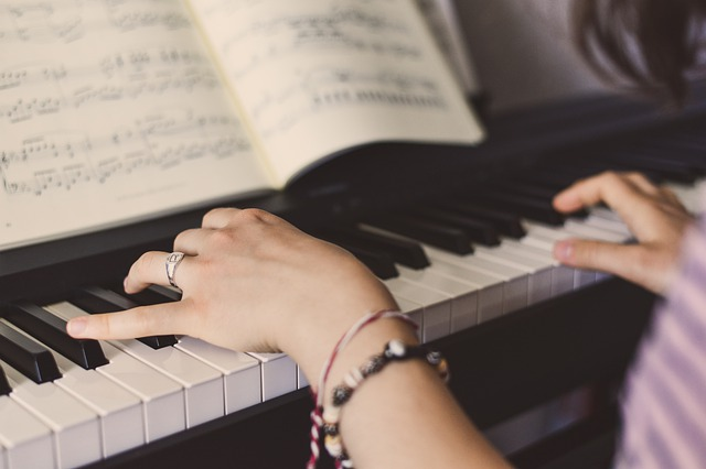 woman playing piano with sheet music