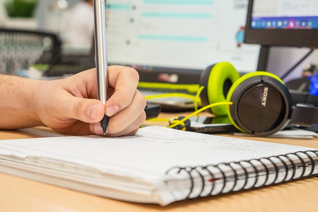 hand writing on pad of paper with headphones and laptop on desk