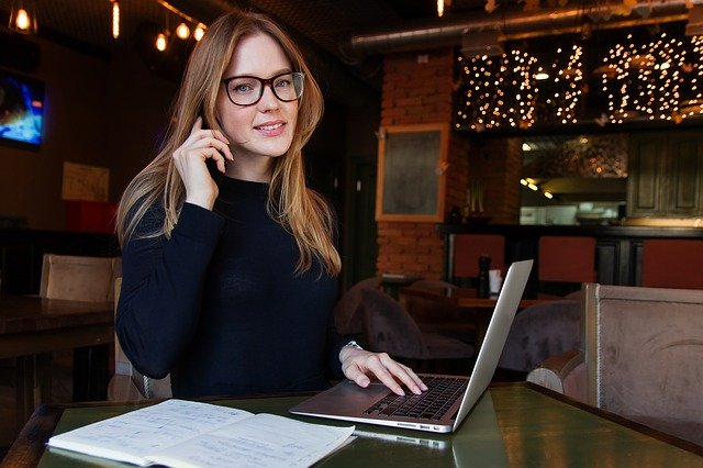 Woman with glasses making phone call and using laptop in venue