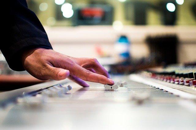 man adjusting mixing board in music studio
