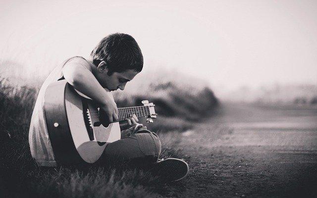 Boy playing guitar in field