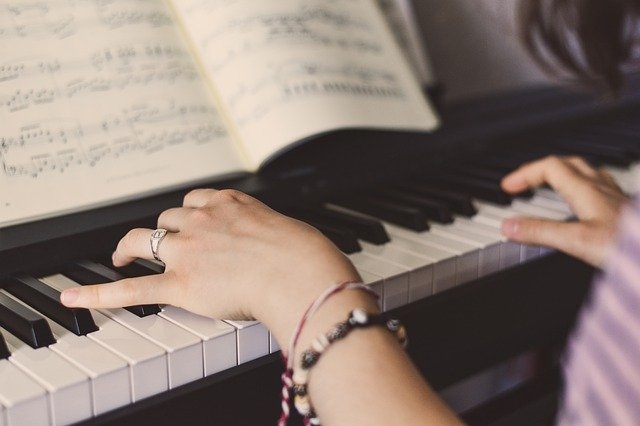 Close-up of woman's hands playing an upright piano with sheet music